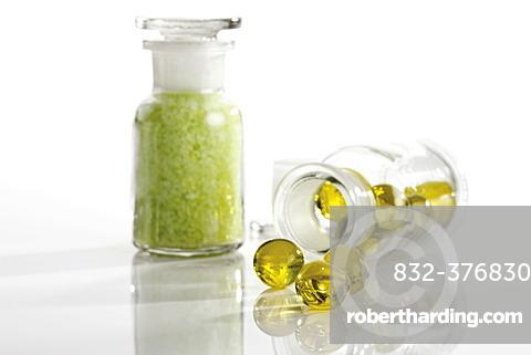 Glass bottles containing golden bath oil beads and green bath salt crystals