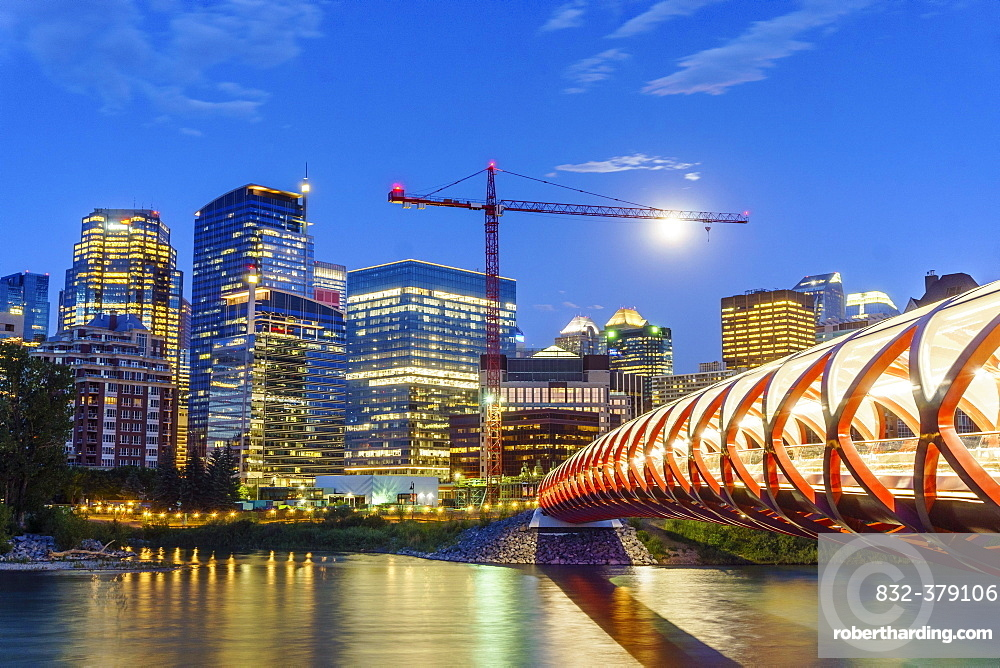Calgary downtown at dusk with Peace Bridge over Bow river, Alberta, Canada, North America