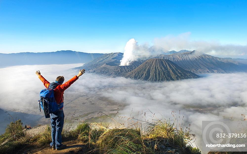 Young man with raised arms in front of volcanic landscape, view in Tengger Caldera, smoking volcano Gunung Bromo, in front Mt. Batok, in the back Mt. Kursi, Mt. Gunung Semeru, National Park Bromo-Tengger-Semeru, Java, Indonesia, Asia