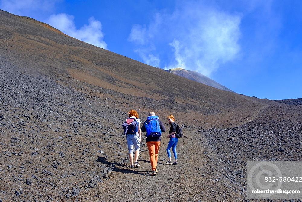 Hikers climbing through volcanic landscape, Volcano Etna, Province of Catania, Silzilia, Italy, Europe
