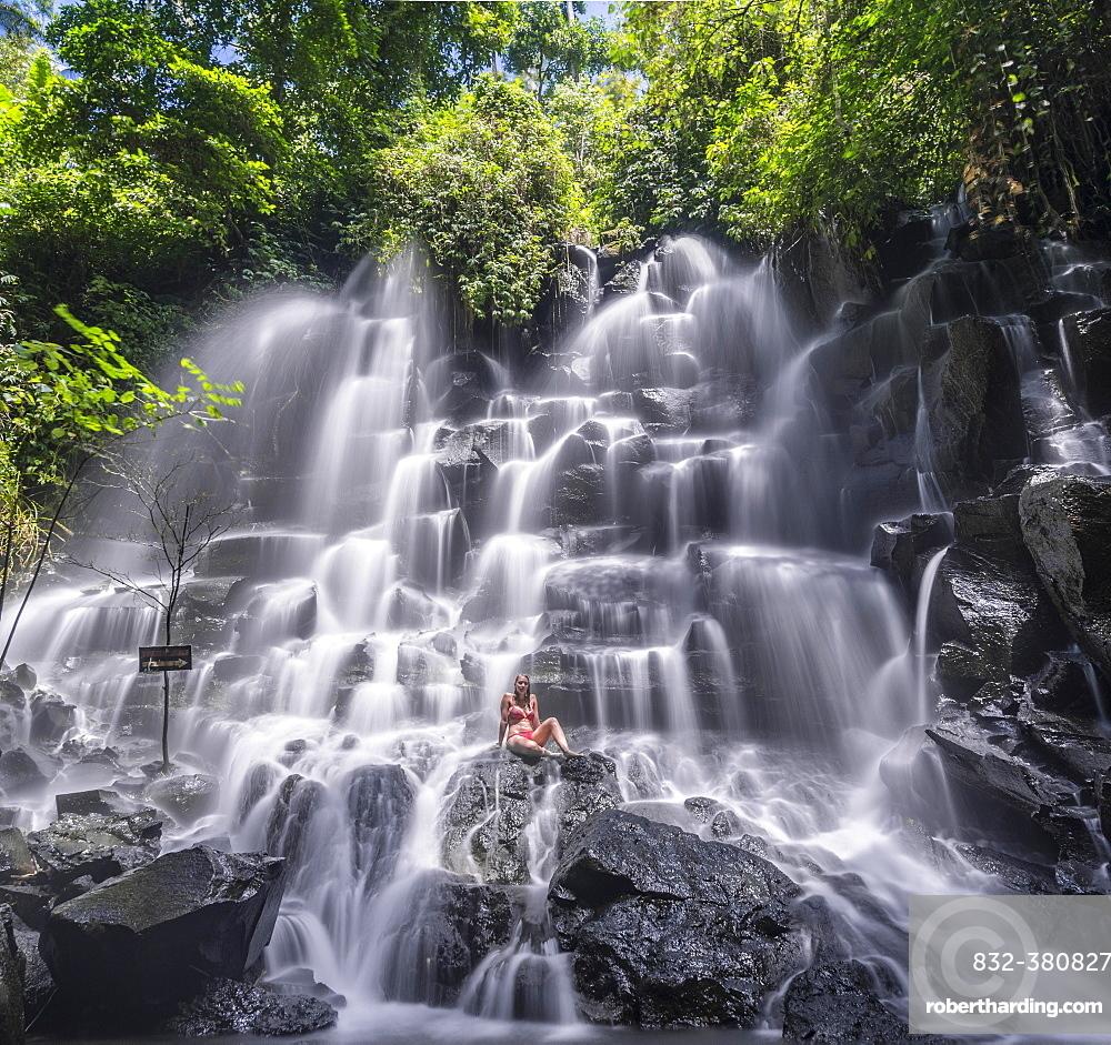 Woman sitting on rock, waterfall, Air Terjun Kanto Lampo, near Ubud, Bali, Indonesia, Asia