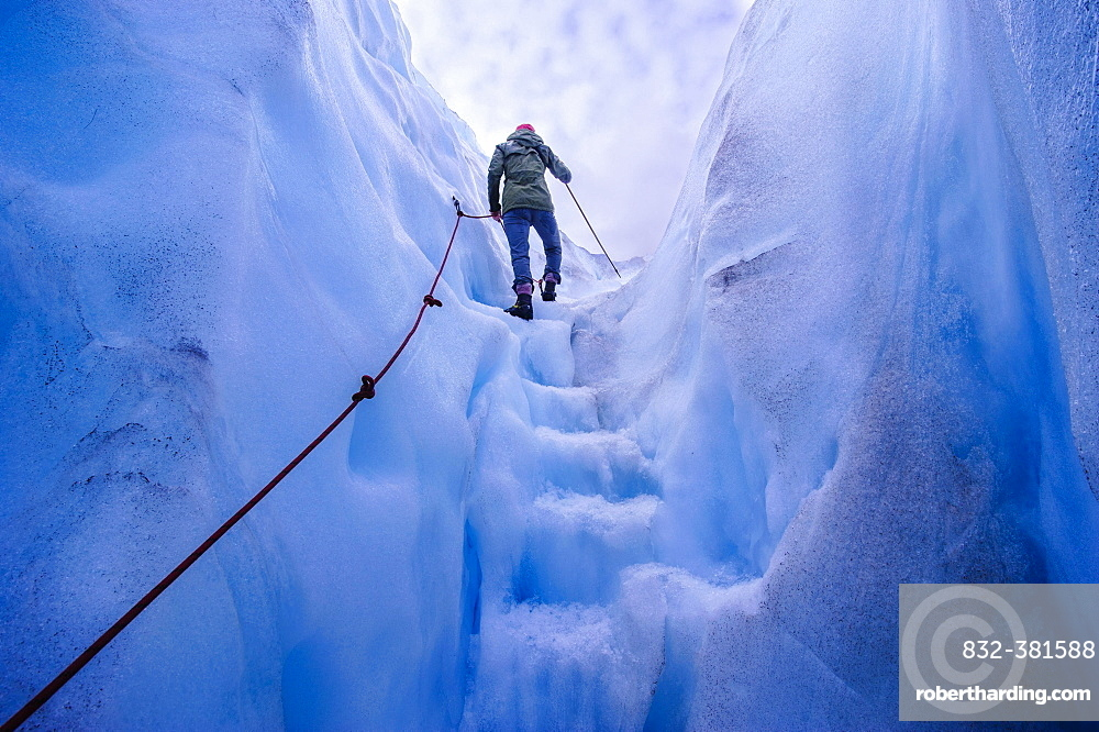 Woman walking steps out of a ice cave in Fox Glacier, South Island, New Zealand, Oceania