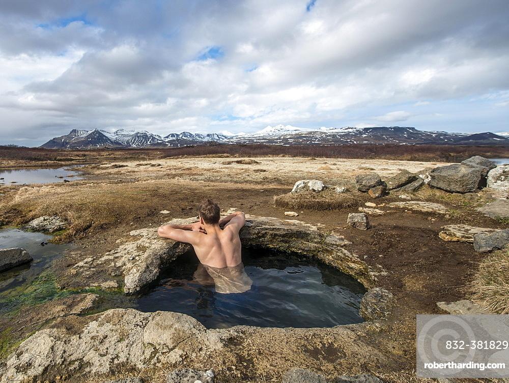 Young man in a hot spring, near Eyjar og Miklaholt, Vesturland, Iceland, Europe