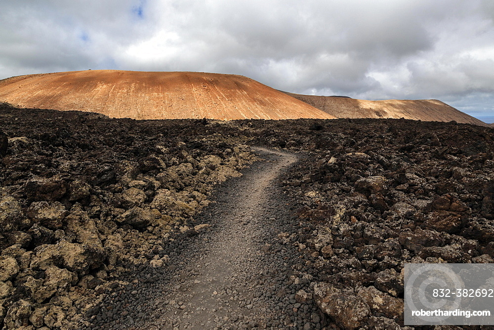 Path through a lava field, volcanic landscape, Fire Mountains, volcanoes, Caldera Blanca volcano at the back, Lanzarote, Canary Islands, Spain, Europe