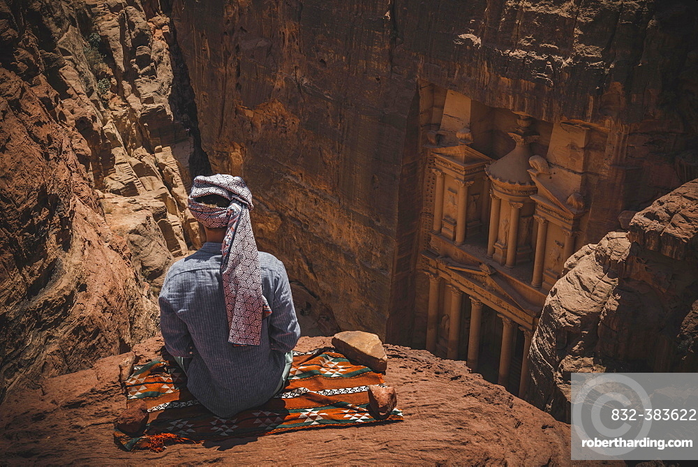 Tourist with turban sits on carpet and looks from above into the canyon Siq, Pharaoh's treasure house beaten into rock, facade of the treasure house Al-Khazneh, Khazne Faraun, mausoleum in the Nabataean city Petra, near Wadi Musa, Jordan, Asia