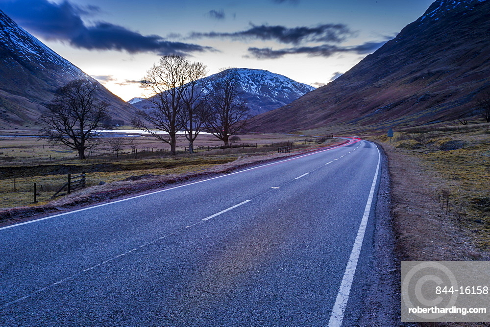 View of road through the Glencoe Valley at dusk, Glencoe, Highland Region, Scotland, United Kingdom, Europe