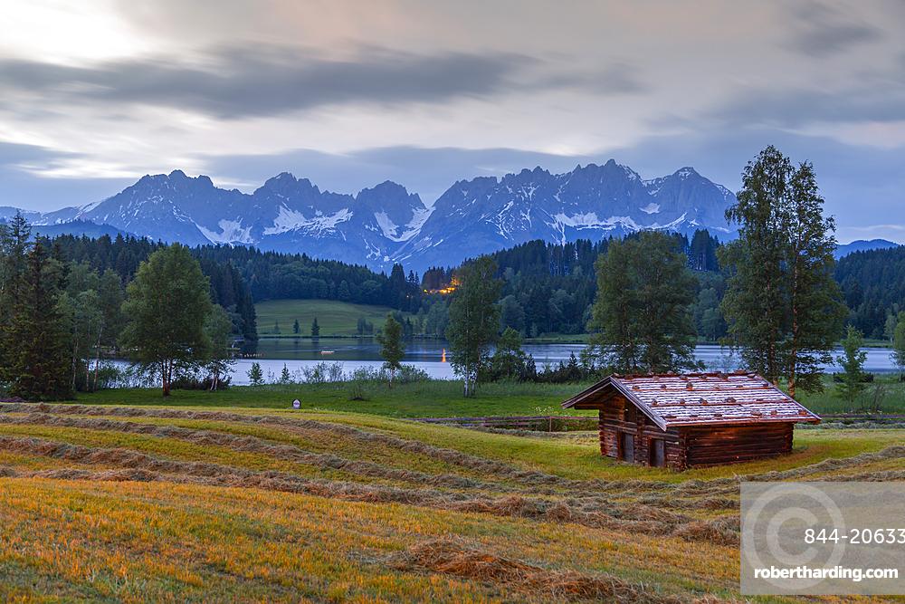 View of traditional log cabin and Kaiser Mountain Range backdrop at Schwarzsee near Kitzbuhel, Austria, Europe