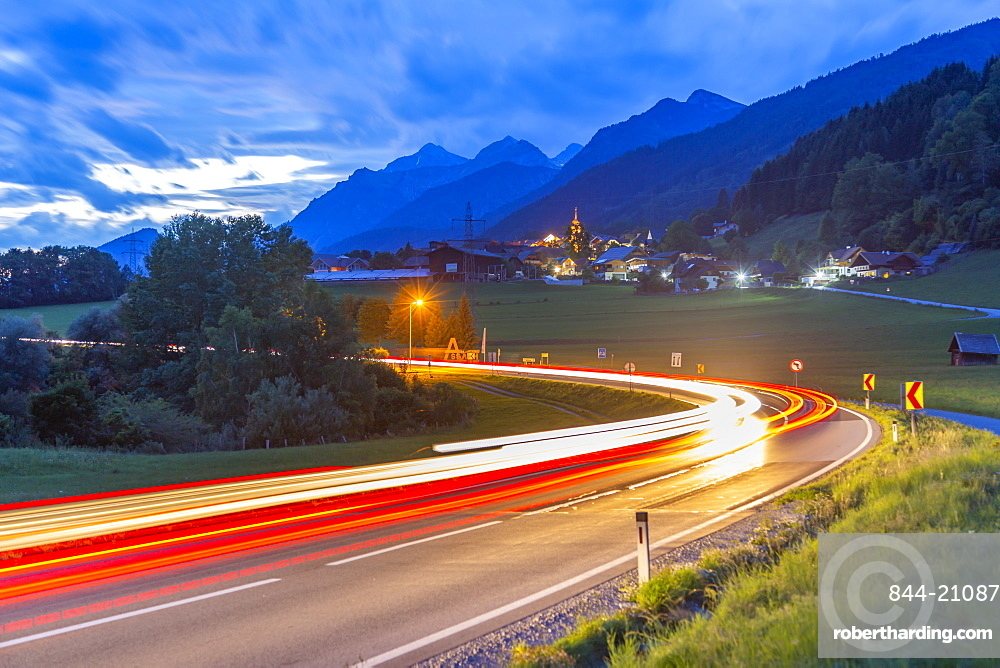 View of winding road and trail lights at dusk near Oberhaus, Styria, Austria, Europe