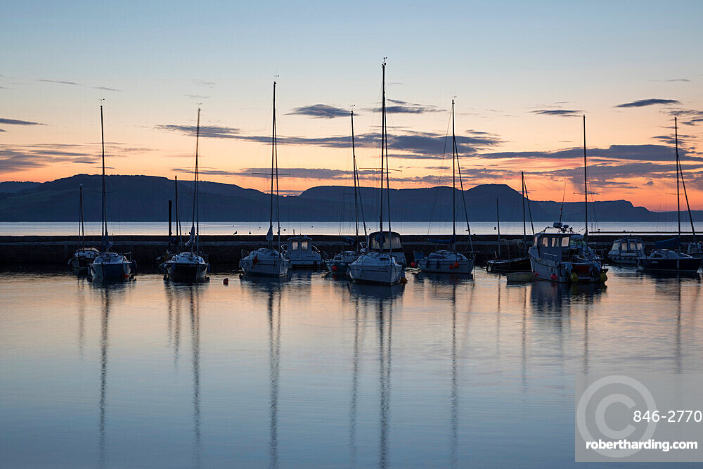 Yachts moored in The Cobb with Jurassic Coast and Golden Cap at sunrise, Lyme Regis, Dorset, England, United Kingdom, Europe