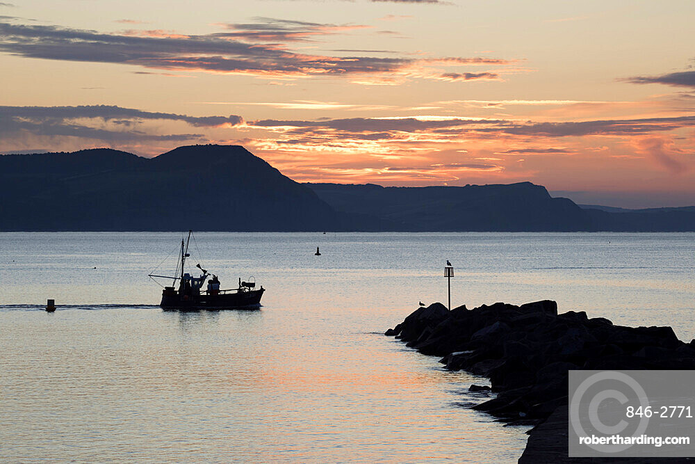 Fishing boat sailing past The Cobb at sunrise with Golden Cap and Jurassic Coast, UNESCO World Heritage Site, Lyme Regis, Dorset, England, United Kingdom, Europe