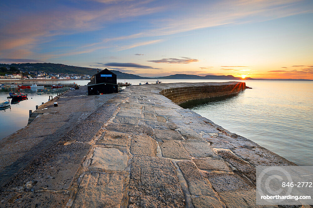 The Cobb with the cliffs of Jurassic Coast at sunrise, Lyme Regis, Dorset, England, United Kingdom, Europe