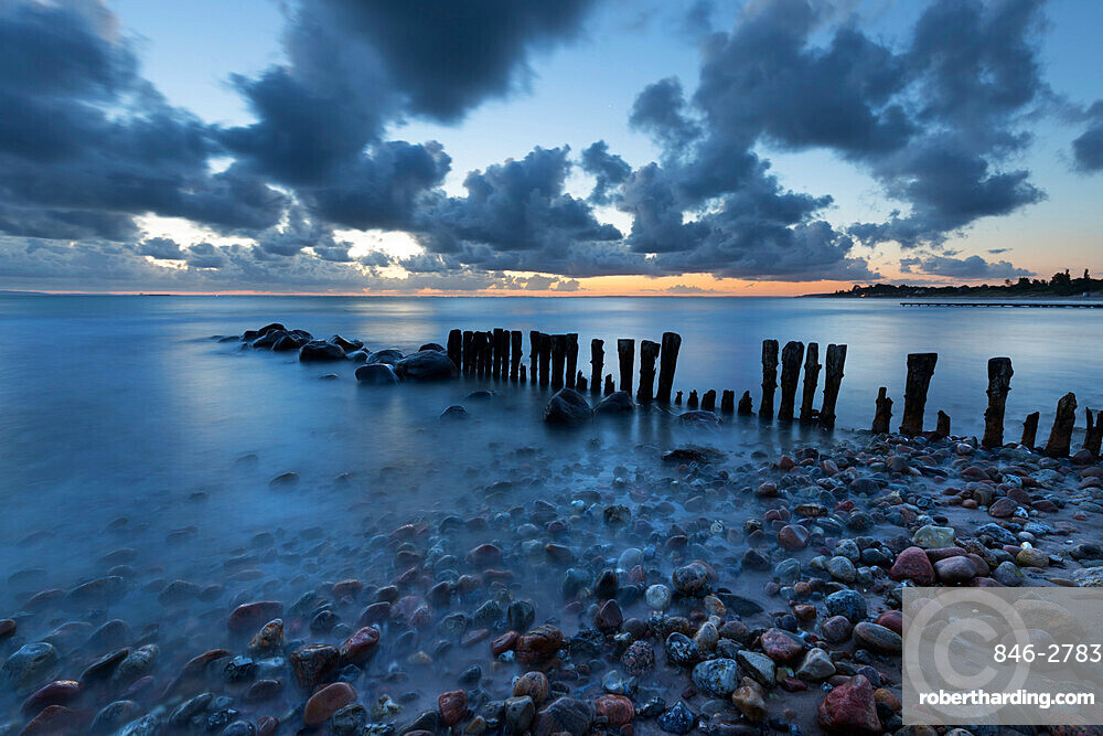 Old wooden piles going out to sea and pebbles on beach at dawn, Munkerup, Kattegat Coast, Zealand, Denmark, Scandinavia, Europe