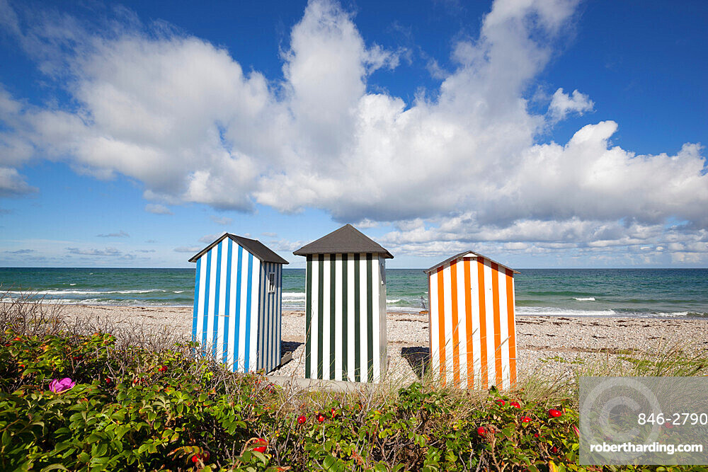 Colourful beach huts on pebble beach with blue sea and sky with clouds, Rageleje, Kattegat Coast, Zealand, Denmark, Scandinavia, Europe