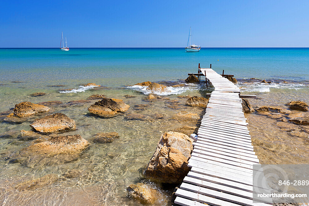 Wooden pier and clear turquoise sea with yachts at Provatas beach, Milos, Cyclades, Aegean Sea, Greek Islands; Greece; Europe