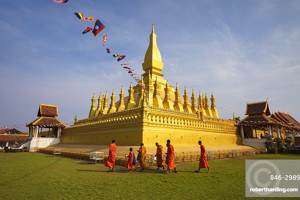 The golden Buddhist stupa of Pha That Luang with Buddhist monks walking below, Vientiane, Laos, Southeast Asia