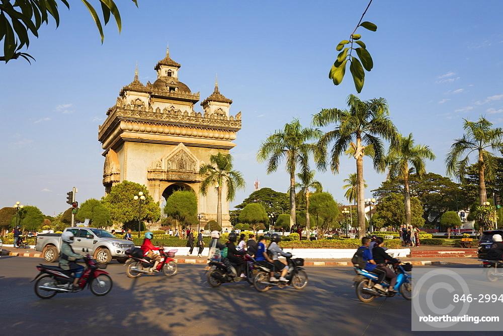 Mopeds riding past the Patuxai Victory Monument (Vientiane Arc de Triomphe), Vientiane, Laos, Southeast Asia