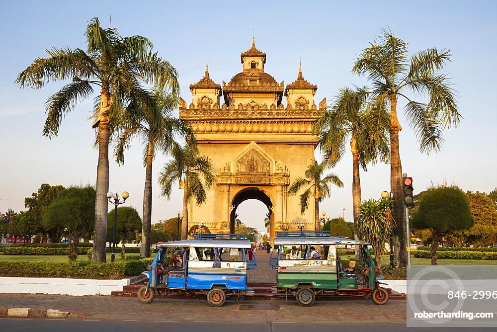 Tuk-tuks parked in front of the Patuxai Victory Monument (Vientiane Arc de Triomphe), Vientiane, Laos, Southeast Asia