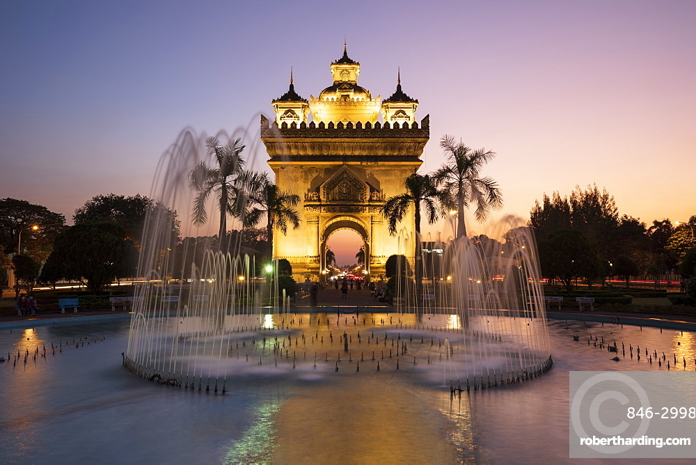 Patuxai Victory Monument (Vientiane Arc de Triomphe) and fountain floodlit at dusk, Vientiane, Laos, Southeast Asia