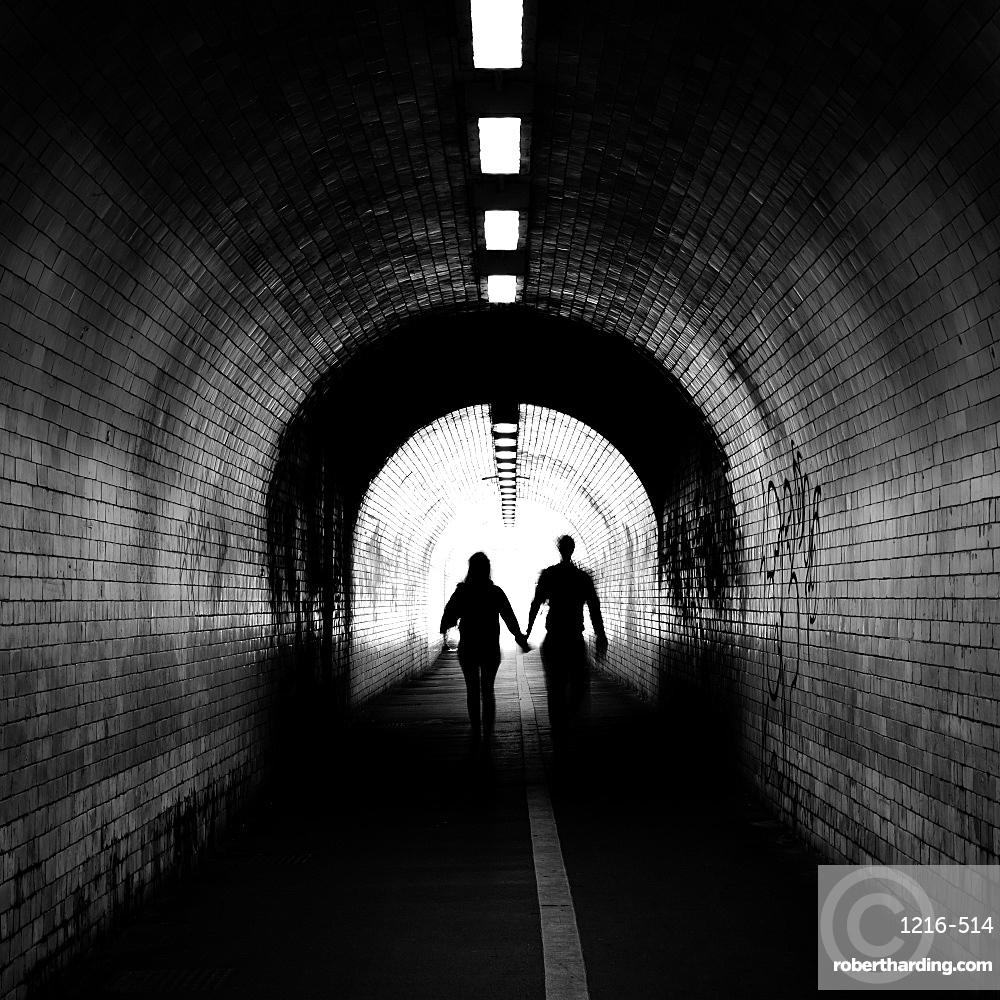 Couple walking into the light, York tunnel, York, England, UK