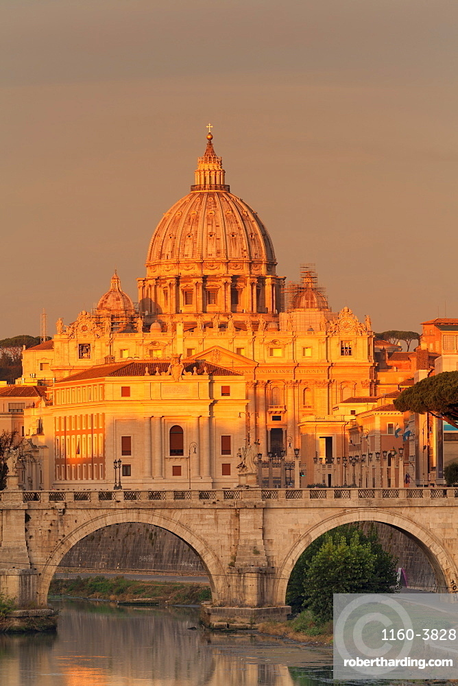 View over Tiber River to Ponte Vittorio Emanuele II Bridge and St Peter's Basilica at sunrise, Rome, Italy