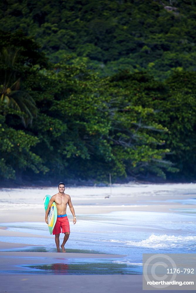 Brazilian male surfer with a Brazilian flag surfboard on a beach in Rio de Janeiro state, Brazil, South America