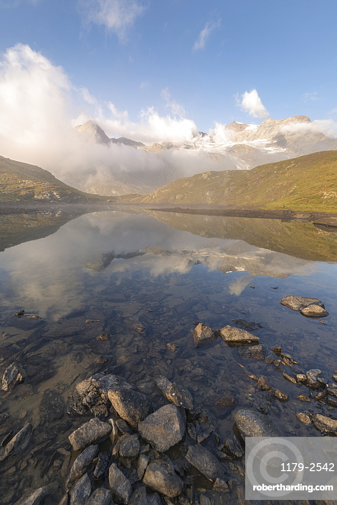 Peaks of mountain range reflected in alpine lake, Bernina Pass, Poschiavo Valley, Engadine, Canton of Graubunden, Switzerland, Europe