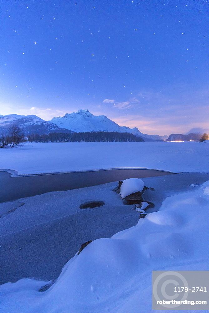 Stars above Piz Da La Margna and icy Lake Sils, Maloja, Engadine, Canton of Graubunden, Switzerland, Europe