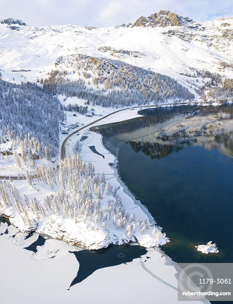 Aerial panoramic view of road around frozen Lake Sils, Plaun da Lej, Maloja Region, Canton of Graubunden, Engadine, Switzerland, Europe (Drone)