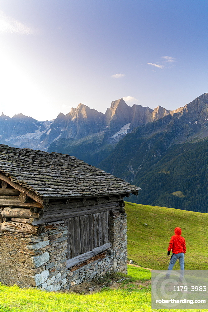 Rear view of man out of a stone hut looking at Piz Cengalo and Badile, Tombal, Val Bregaglia, canton of Graubunden, Switzerland