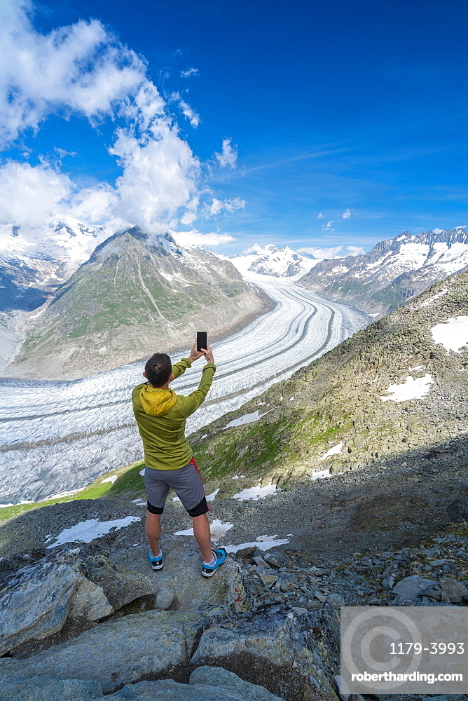 Rear view of man photographing Aletsch Glacier with smartphone from Eggishorn viewpoint, Bernese Alps, canton Valais, Switzerland