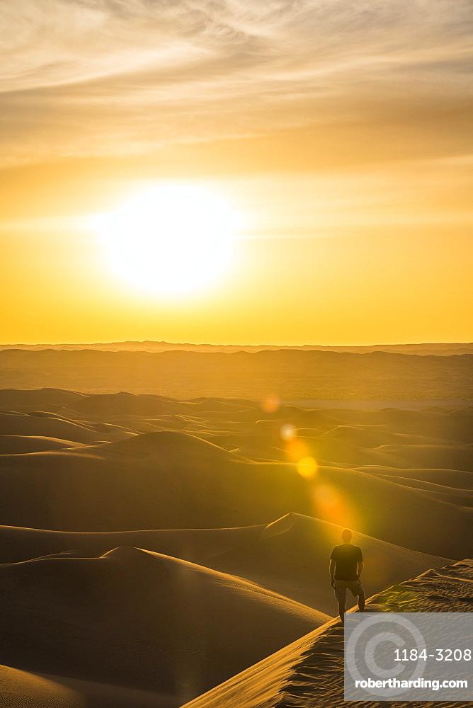 Man enjoying the sunset in the giant sand dunes of the Sahara Desert, Timimoun, western Algeria, North Africa, Africa