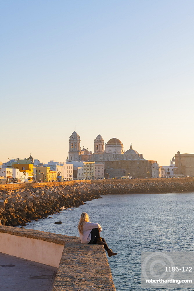 Woman enjoying the view of Santa Cruz Cathedral and ocean seen from the promenade along quayside, Cadiz, Andalusia, Spain, Europe