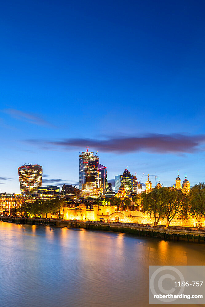 The city and tower of London at dusk reflecting in the river Thames