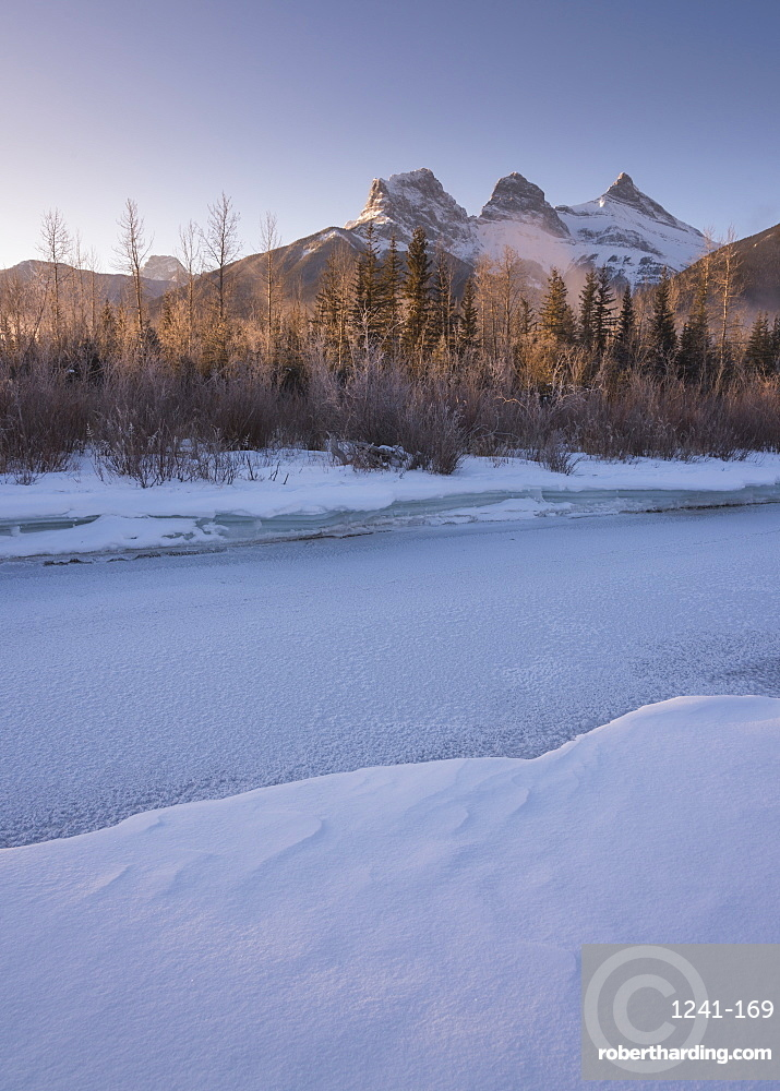 Winter sunrise with frozen Bow River and Three Sisters, Canmore, Alberta, Canadian Rockies, Canada, North America