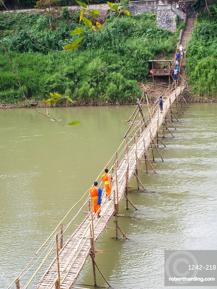 Orange-clad Buddhist monks crossing a bamboo bridge, Luang Prabang, Laos, Indochina, Southeast Asia, Asia