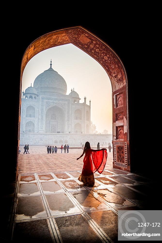 A lady twirls as the sun rises behind the Taj Mahal, UNESCO World Heritage Site, Agra, Uttar Pradesh, India, Asia