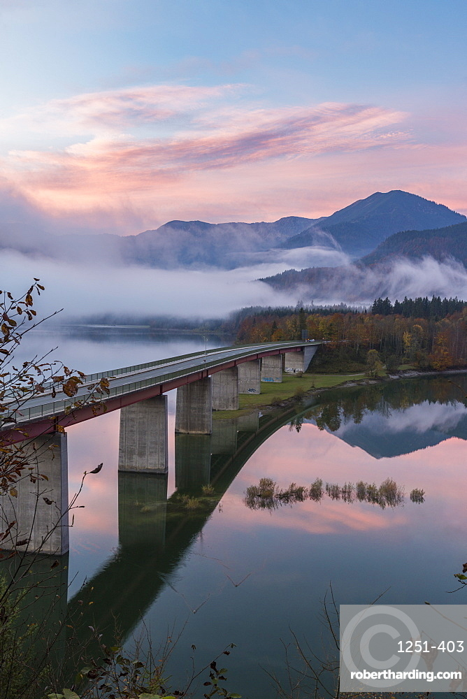 Sylvenstein Lake and bridge surrounded by the morning mist at dawn. Bad Tölz-Wolfratshausen district, Bavaria, Germany.