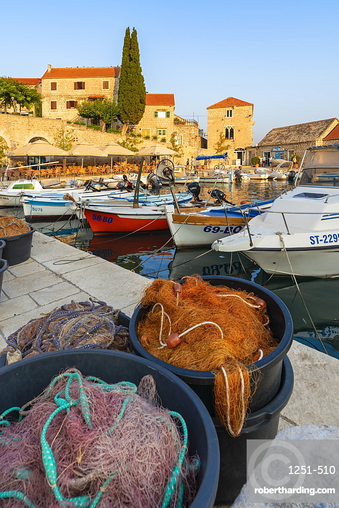 Boats and fishing nets at the pier of the town at sunset. Bol, Brac island, Split - Dalmatia county, Croatia.