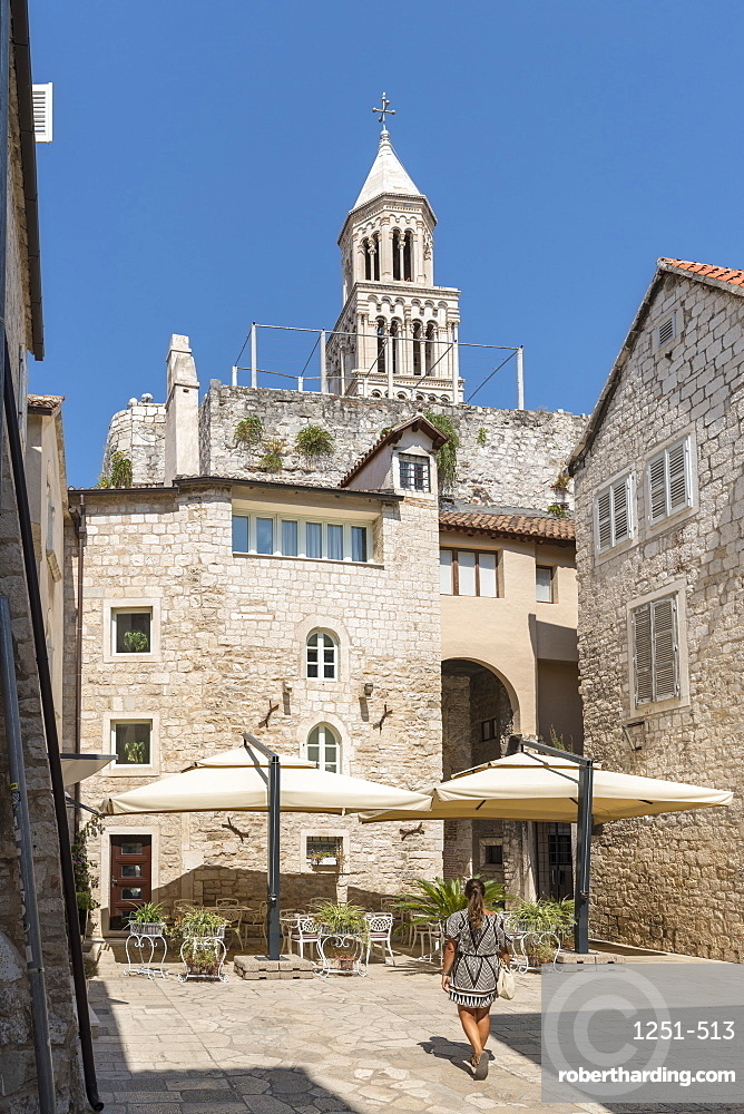Woman walking in summer, with the bell tower of St Domnius Cathedral in the background. Split, Split - Dalmatia county, Croatia.