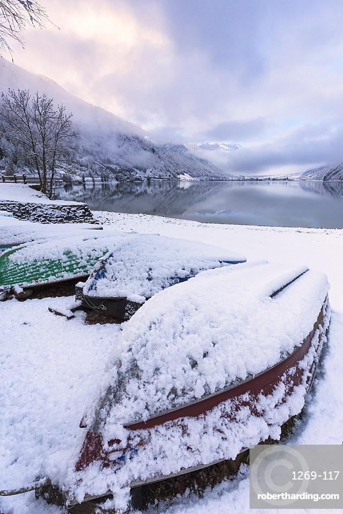 Boats covered by snow at Poschiavo Lake. Lago di Poschiavo, Poschiavo Valley(Val Poschiavo), Graubünden, Switzerland, Europe.