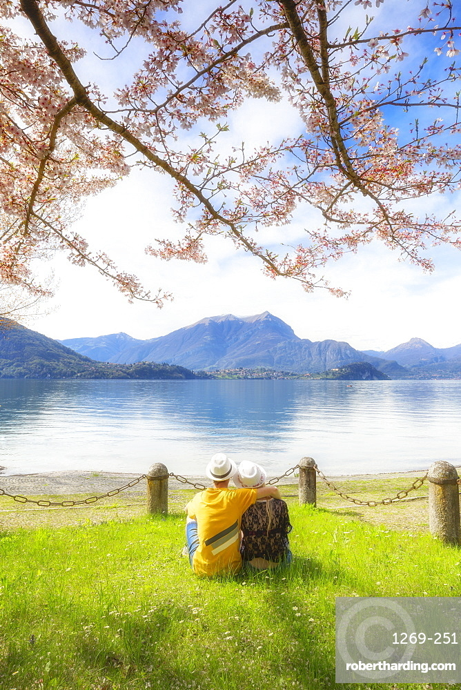 Couple of tourists sitting in frontof the lake. Lierna, Province of Lecco, Lake Como, Italian Lakes, Lombardy, Italy, Europe