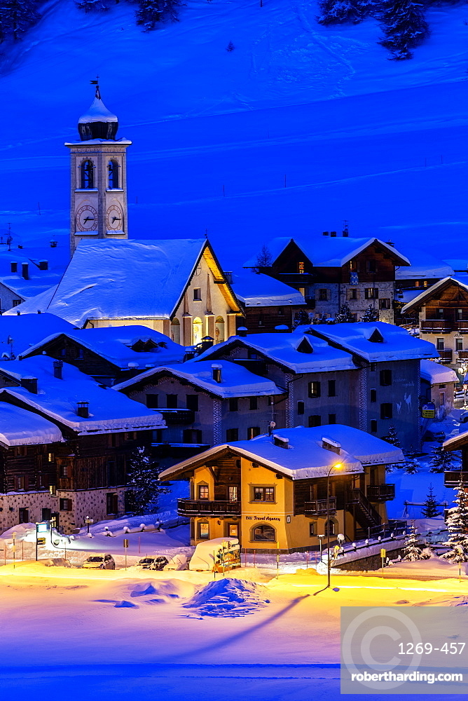 Church and houses illuminated during a winter twilight, Livigno, Valtellina, Lombardy, Italy, Europe