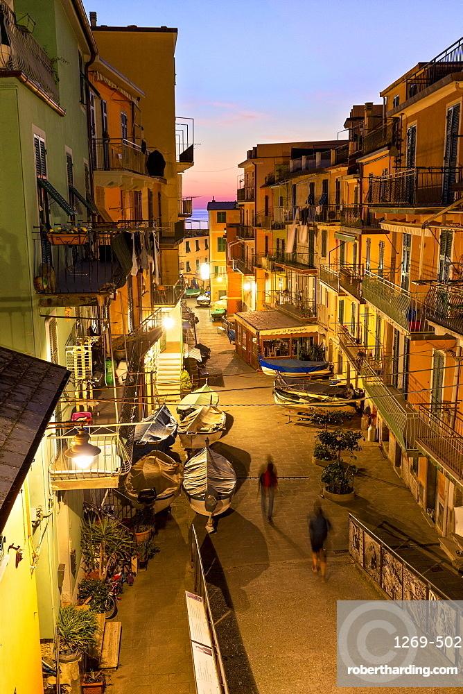 Tourists walks in the main street of Manarola at dusk, Cinque Terre, UNESCO World Heritage Site, Liguria, Italy, Europe