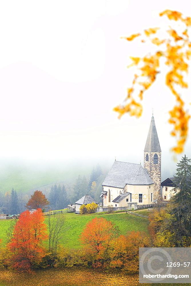 Church of Santa Magdalena in the autumn mist. Funes Valley, Sudtirol, Dolomites, Italy