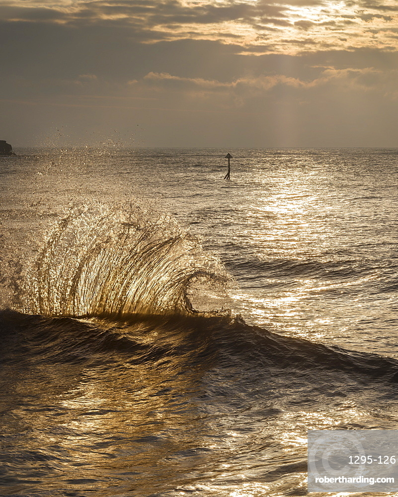 Waves backlit by the dawn sun reflect off the sea wall and impact with an incoming one - Exmouth, Devon, UK.