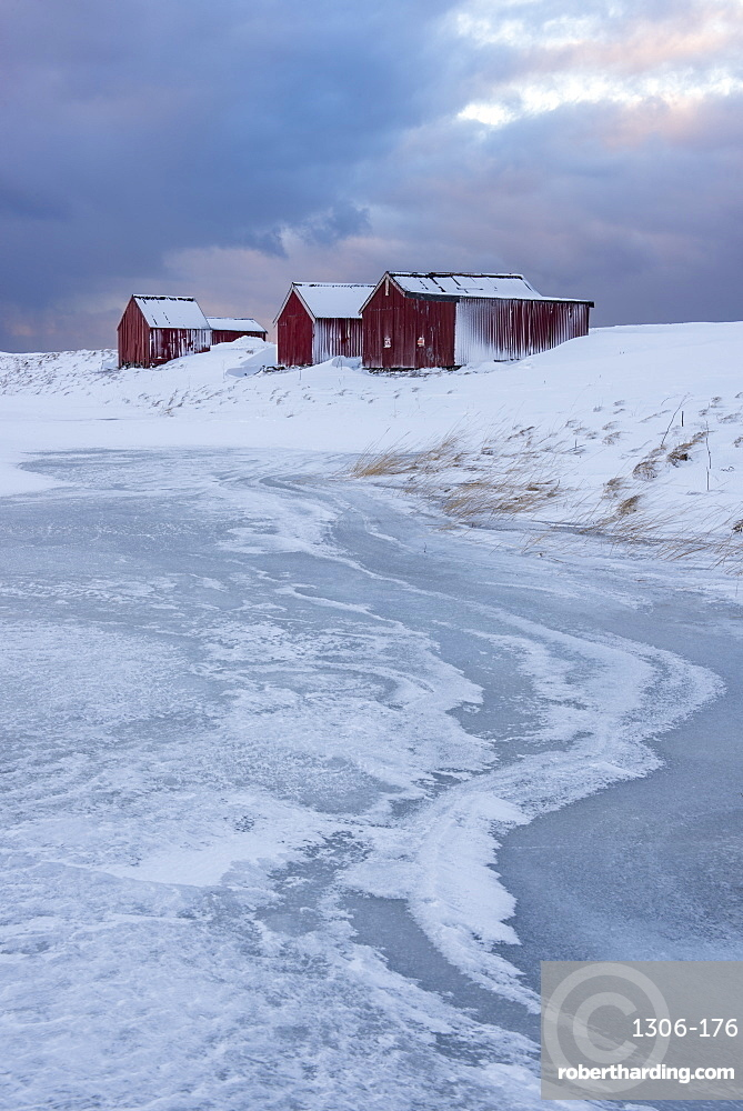 Fishermans houses and ice formations with dramatic sky in winter, Eggum, Lofoten Islands, Arctic, Norway, Europe