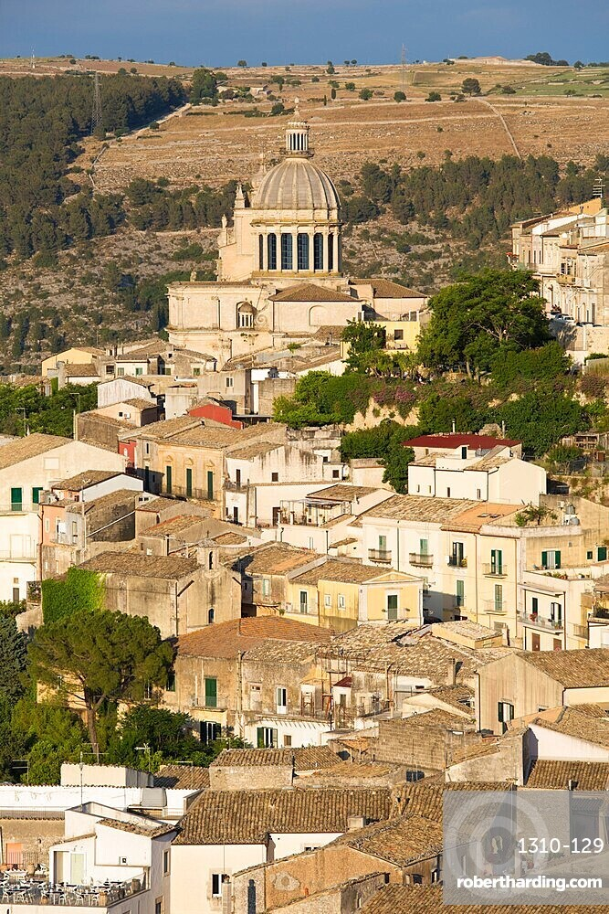View over the sunlit rooftops of Ragusa Ibla, evening, dome of the Cathedral of San Giorgio prominent, Ragusa, Sicily, Italy