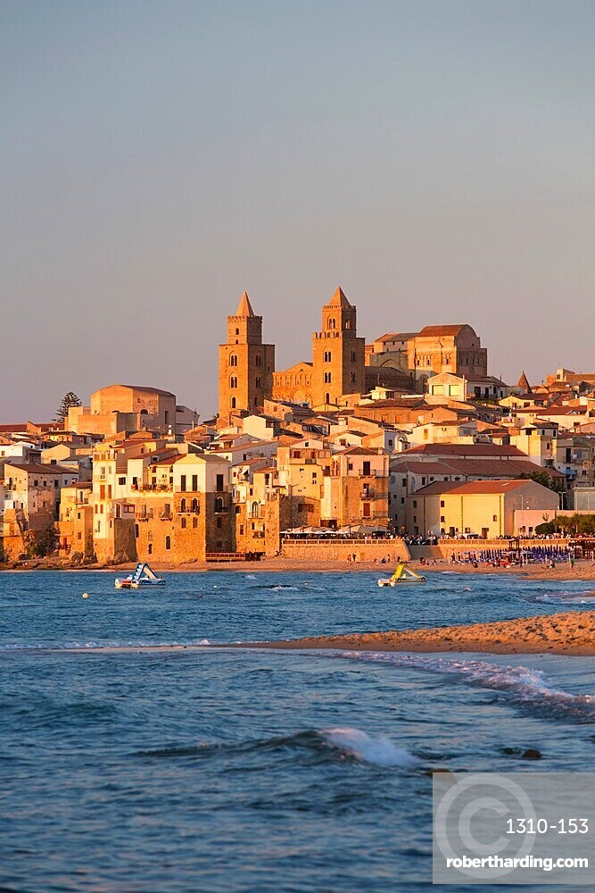 View from beach along water's edge to the town and UNESCO listed Arab-Norman cathedral, sunset, Cefalu, Palermo, Sicily, Italy