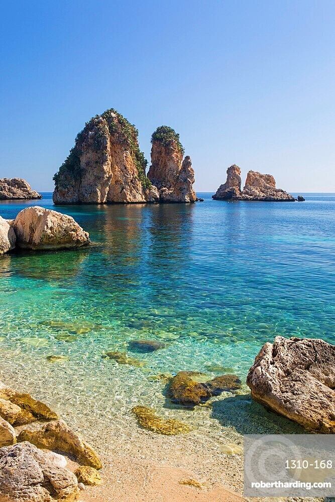 View across tranquil cove to the Faraglioni, a series of towering offshore rock stacks, Scopello, Trapani, Sicily, Italy
