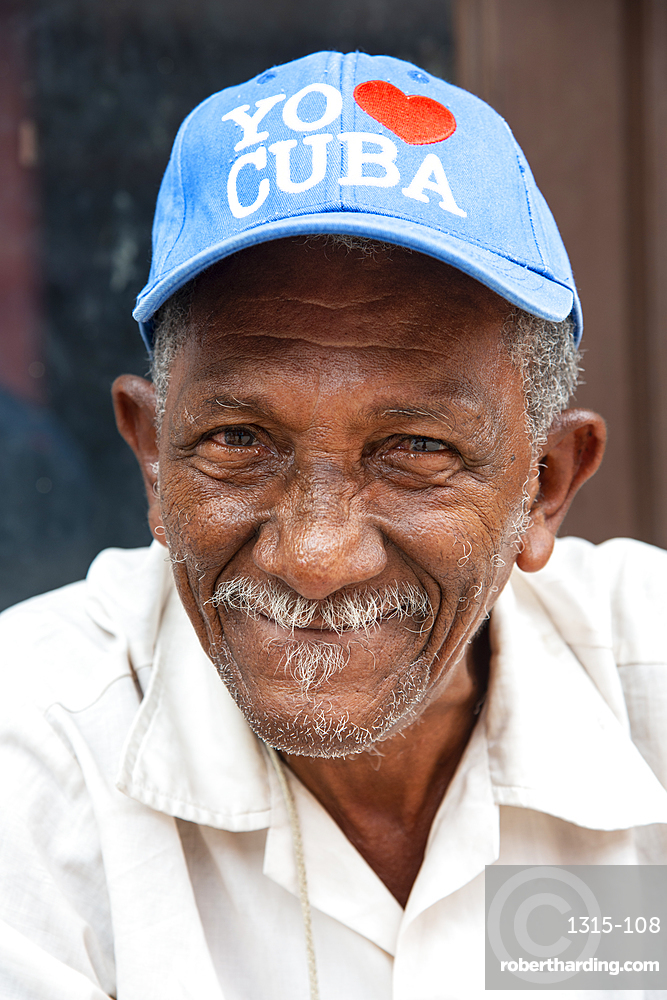 Local man wearing an I love Cuba hat relaxing on the street in Trinidad, Cuba, West Indies, Caribbean, Central America